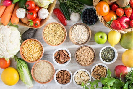 Variety of fruits and vegetables, cereals, nuts on the white wooden table, top view, selecitve focus. Stock Photo