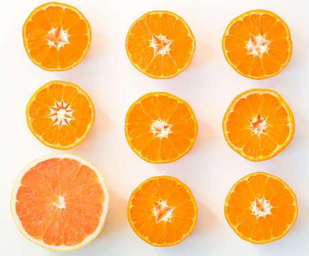 Top view of eight slices of satsuma and one slice of grapefruit, on the white background Stock Photo