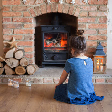 woodburner: Little girl sitting in front of the fireplace looking at the fire flame in the woodburner, selective focus