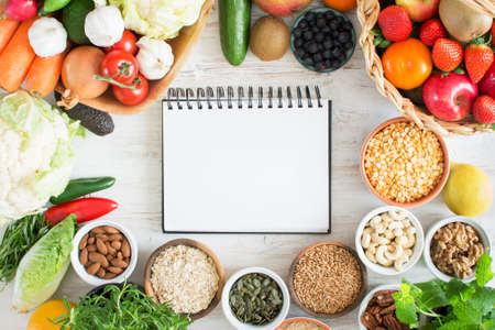 Variety of fruits and vegetables, cereals, nuts on the white wooden table, top view, copy space for text, selecitve focus. Basket of strawberries, apples, oranges, kiwi, bowls of oats, spelt, rice, kamut, peas; broccoli, cauliflower, garlic, tomatoes, pep