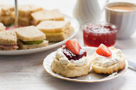 Té de la tarde inglés tradicional: bollos con crema y mermelada coagulada, fresas, con varios sadwiches en el fondo, enfoque selectivo