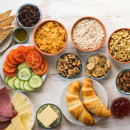 Top view of the healthy filling breakfast, ham, cheese, cereals, toast, nuts, jam, vegetables, croissants, selective focus