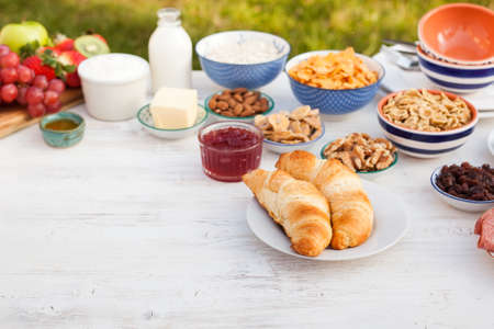 picnic food: Healthy continental  breakfast served in the garden, ham, cheese, cereals, nuts, jam, vegetables, croissants, selective focus, copy space for text