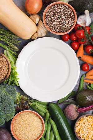 Colourful vegetables and grains, arranged in a circle with off white plate in the middle, broccoli, squash, beans, tomatoes, carrots, avocado, top view, vertical selective focus