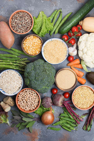Above view of grains in bowls and vegetables, broccoli, squash, beans, tomatoes, carrots, avocado, quinoa, peas, rice, oats, selective focus