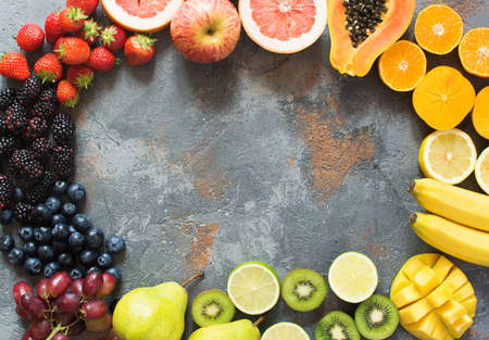 DIfferent rainbow colored fruits and berries arranged in a circle, on the grey stone background, copy space for text, selective focus Stock Photo
