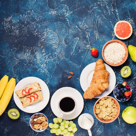 danish: Top view of breakfast on blue concrete table, pancakes with berries, cereals, oats, banana, grapes, croissant, nuts with coffee, selective focus, copy space