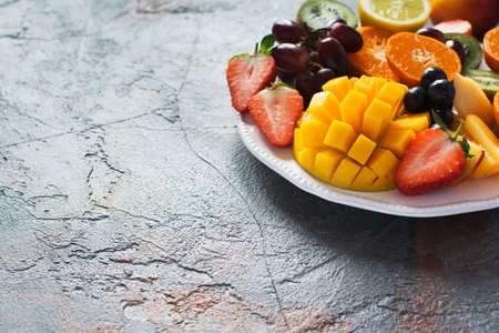 Sliced fruits and berries on white plate on the grey stone background, copy space, selective focus
