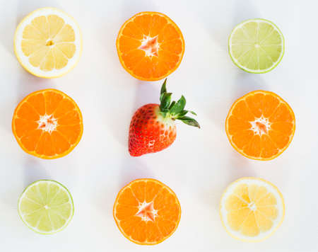 Top view of eight slices of citrus fuits and one strawberry, on the white background