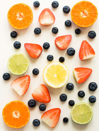 Top view of citrus fuits and strawberies, blueberries on the white background