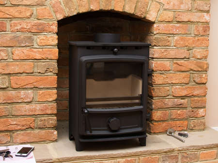 Logburner installation in process: fitting the woodburner into the fireplace, selective focus