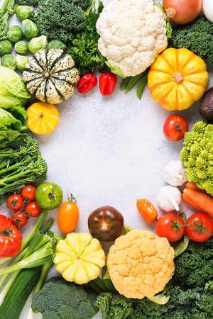 Colorful vegetables arranged in a circle frame on the light grey background, copy space for text in the middle, vertical, selective focus