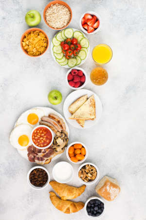 Full English breakfast, eggs, bacon, sausages, breads and fruits Stock Photo