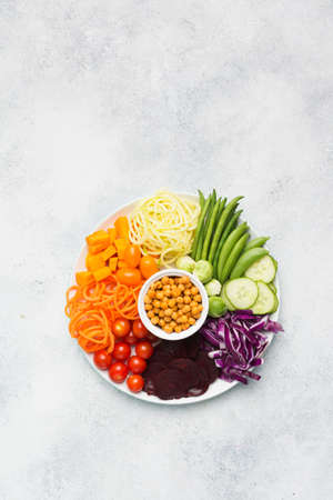 Healthy eating, top view of buddha bowl, rainbow vegetables, carrot, courgette, cabbage, chickpeas, cucumber and tomatoes, on wooden board on white table, copy space, top view, selective focus