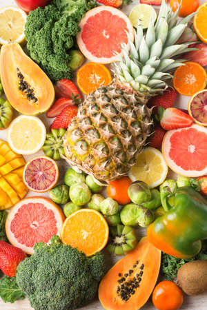 Fruits and vegetables rich in vitamin C background pattern, oranges mango grapefruit kiwi kale pepper pineapple lemon sprouts papaya broccoli, vertical, on white table, top view, selective focus