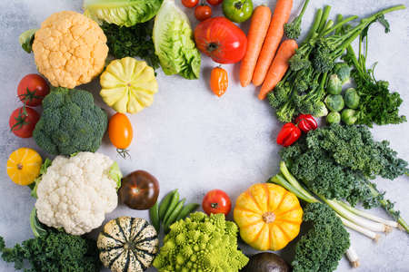 Various colorful vegetables arranged in a circle on the light grey background, copy space for text in the middle, selective focus Stock fotó