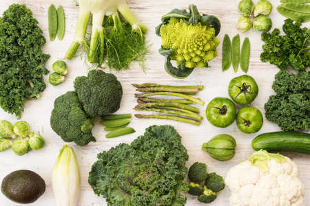 Assortment of green vegetables on the white wooden table arranged in a grid, horizontal, top view, selective focus 写真素材