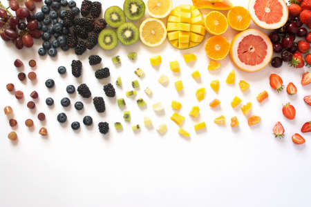 Top view of whole fruits and cut slices in the rows, red, orange, yellow, green fruits with cut pieces on the white background, grapefruit, mango, strawberries, orange, lemon, kiwi