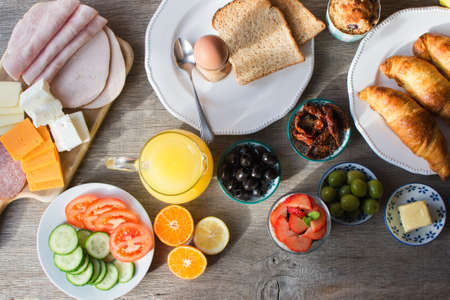 Healthy breakfast selection: yogurt with nuts and berries, with olives, tomatoes, cucumbers, ham, cheese, bread, croissants, orange juice, top view, selective focus