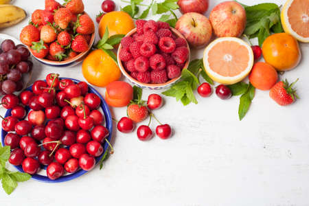 Summer fruits and berries, strawberries, cherries, raspberries, oranges, grapes, persimmon on a white table, space for text, selective focus