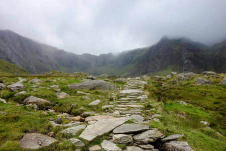 Walking path in Snowdonia National Park, North Wales, United Kingdom, view of the mountains in a cold foggy weather, selective focus