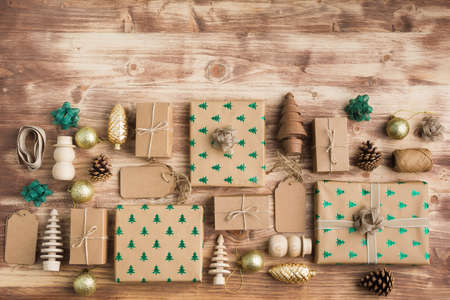 Christmas arrangement, brown present boxes with sparkling embossed fur trees, pine cones, golden baubles, wooden decorations, jute twine, top view, copy space for text Stock Photo