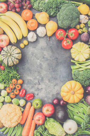 Assortment of vegetables and fruits arranged in a circle on the dark grey background, copy space for text in the middle, top view, vertical, selective focus, toned
