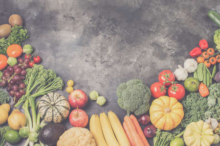 Table top view of different rainbow vegetables and fruits on the light grey background, copy space for text, selective focus, toned