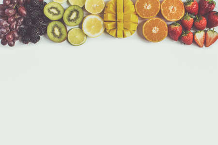 Top view of whole fruits and in the rows; red, orange, yellow, green fruits on the white background; grapefruit, mango, strawberries, orange, lemon, kiwi, toned, copy space