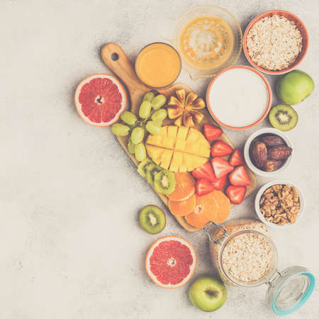 Healthy breakfast with oats, variety of fruits, strawberries, mango, grapes, figs, yogurt and nuts served on the white table, top view, copy space for text, square selective focus, toned