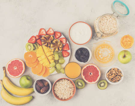 Healthy breakfast with oats, variety of fruits, strawberries, mango, grapes, figs, yogurt and nuts served on the white table, top view, copy space for text, selective focus, toned