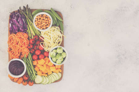 Top view of ingredients for the salad, colourful vegetables, carrot, courgette, cabbage, chickpeas, cucumber and tomatoes, on wooden board on white table, top view, copy space, selective focus, toned