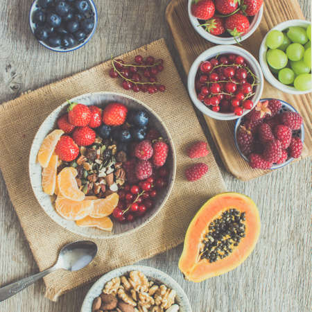 Top view of grain free paleo muesli made with nuts and dried fruits, served with strawberries, blueberries, raspberries, red currants, grapes, square, selective focus, toned