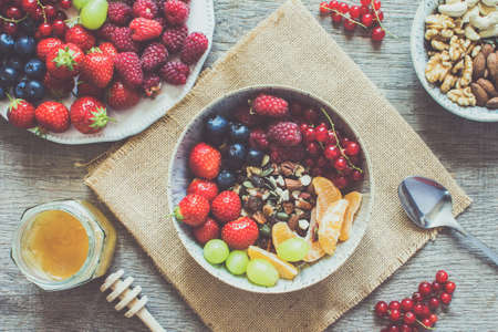 Top view of grain free paleo muesli made with nuts and dried fruits, served with strawberries, blueberries, raspberries, red currants, grapes, selective focus, toned Stock Photo