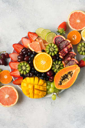 Raw fruits berries platter, mango, oranges, kiwi strawberries, blueberries grapefruit grapes, apples on the white plate, on the off white table, top view, vertical, copy space