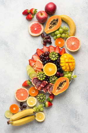 Raw fruits berries platter, mango, oranges, kiwi strawberries, blueberries grapefruit grapes, bananas apples on the white plate, on the off white table, top view, vertical, copy space Stock Photo