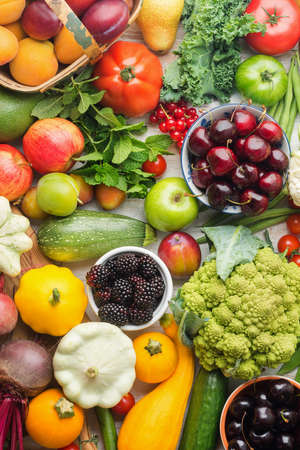 Healthy summer fruits vegetables berries background, cherries peaches strawberries cabbage broccoli cauliflower squash tomatoes carrots spring onions beans beetroot, pepper, top view, vertical Stock Photo