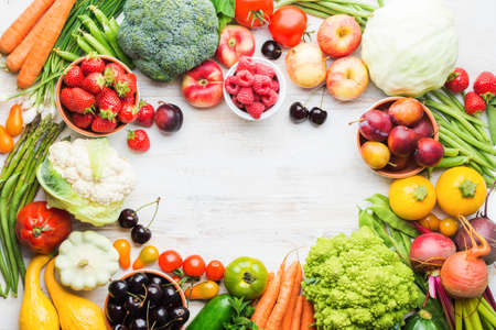 Fresh farm produce frame, fruits vegetables berries, apples cherries peaches strawberries cabbage broccoli cauliflower squash tomatoes carrots beans beetroot copy space, top view, selective focus Stock Photo