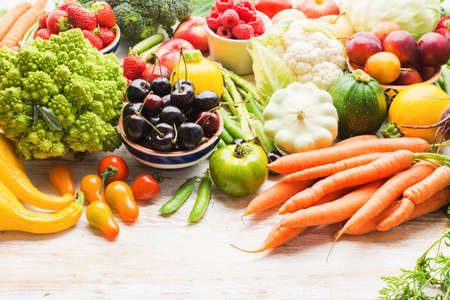 Lots of summer fruits vegetables berries, apples cherries peaches strawberries cabbage broccoli cauliflower squash tomatoes carrots spring onions beans beetroot, copy space, selective focus Stock Photo