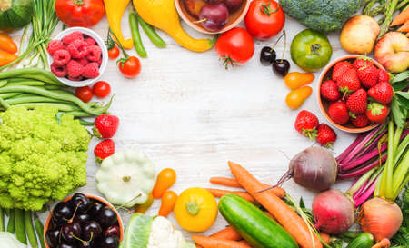 Colourful farm produce, fruits vegetables berries, apples cherries peaches strawberries cabbage broccoli cauliflower squash tomatoes carrots spring onions beans beetroot, copy space, top view Stock Photo