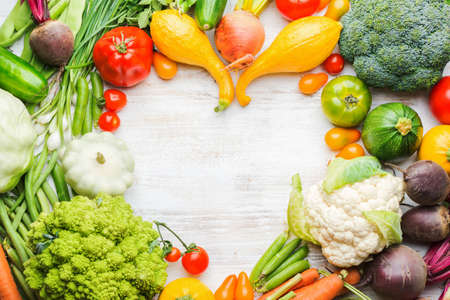 Fresh farm produce, colorful frame made of organic vegetables and herbs on white wooden background, healthy background, copy space for text in the middle, top view, selective focus Stock Photo