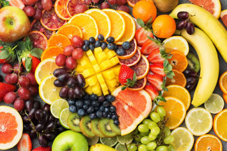 Healthy fruits background oranges apples grapes pears mango strawberries kiwis satsumas, top view, copy space, selective focus