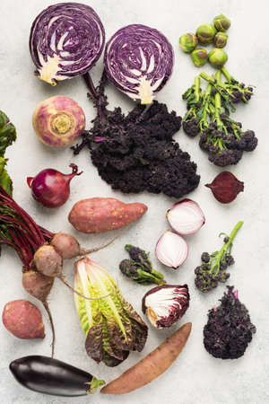 Vegetables background with purple, green and dark red colours, cabbage kale sprouts sweet potato onions broccoli beetroot, top view, off white background, selective focus