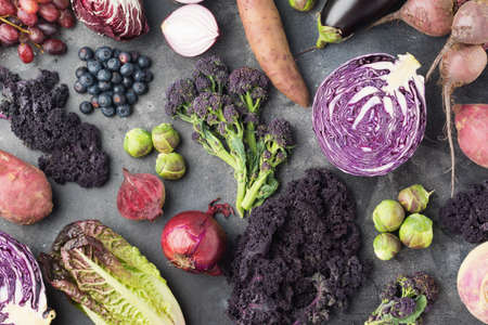 Vegetables and fruits background in purple, green and dark red colours, cabbage kale sprouts sweet potato onions broccoli blueberries grapes, top view, dark grey background, selective focus Stock Photo