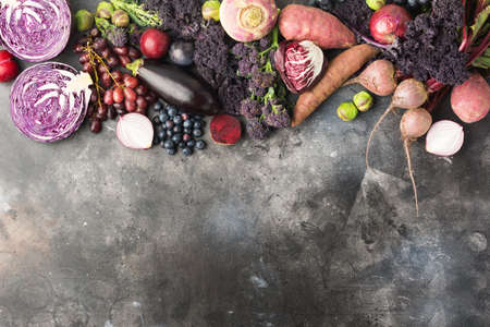 Purple, green and dark red vegetables and fruits background on dark grey, cabbage kale sprouts sweet potato onions broccoli blueberries grapes plums, top view, copy space for text, selective focus