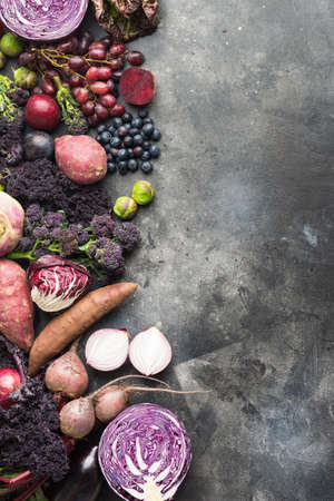 Vertical photo, vegetables and fruits in purple, green and dark red colours, cabbage kale sprouts sweet poato onions broccoli blueberries grapes plums, top view, grey background, selective focus