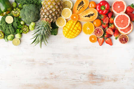 Top view of fruits and vegetables rich in vitamin C in rainbow colors, oranges mango grapefruit kiwi kale pepper pineapple lemon papaya broccoli, on white table, copy space for text, selective focus Stock Photo