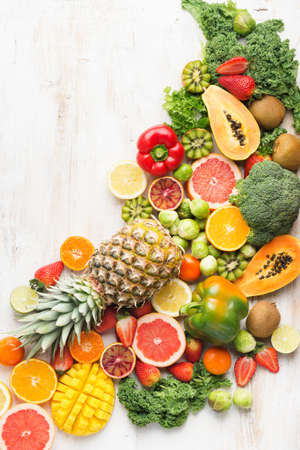 Fruits and vegetables rich in vitamin C arrangement, oranges mango grapefruit kiwi kale pepper pineapple lemon sprouts papaya broccoli, on white table, top view, copy space for text, selective focus Stock Photo