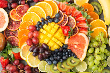 Healthy fruits background in rainbow colours oranges apples grapes pears mango strawberries kiwis on the grey concrete table, top view, selective focus Stock Photo