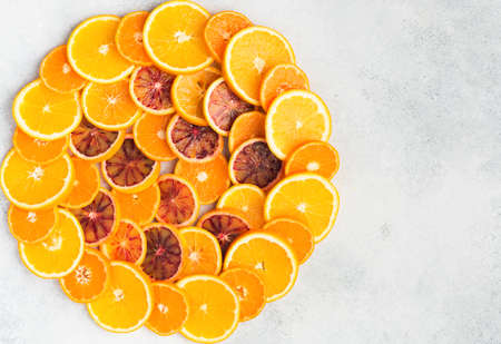 Different varieties of citrus fruits arranged in a circle background on white table, top view, copy space, selective focus Stock Photo
